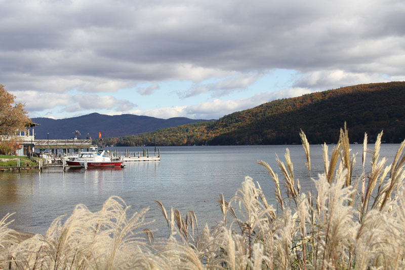 boat docked on lake george with fall foliage in the background