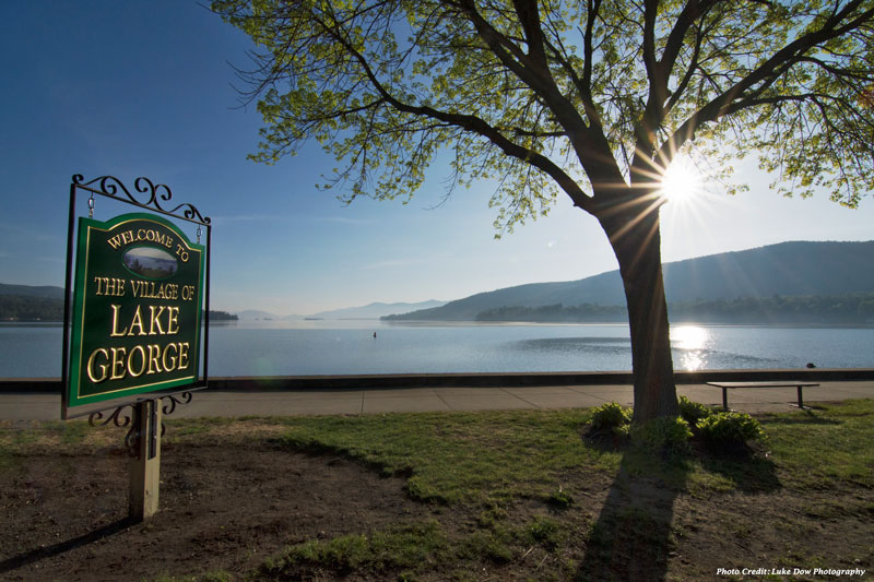 welcome to the village of lake george sign in front of the lake in spring