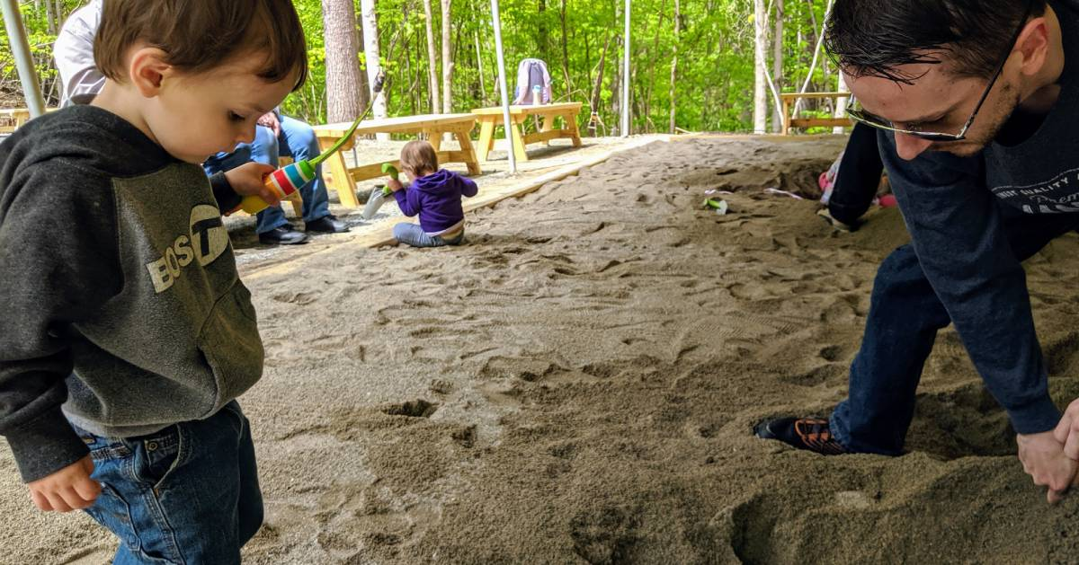 toddler and dad digging through sand