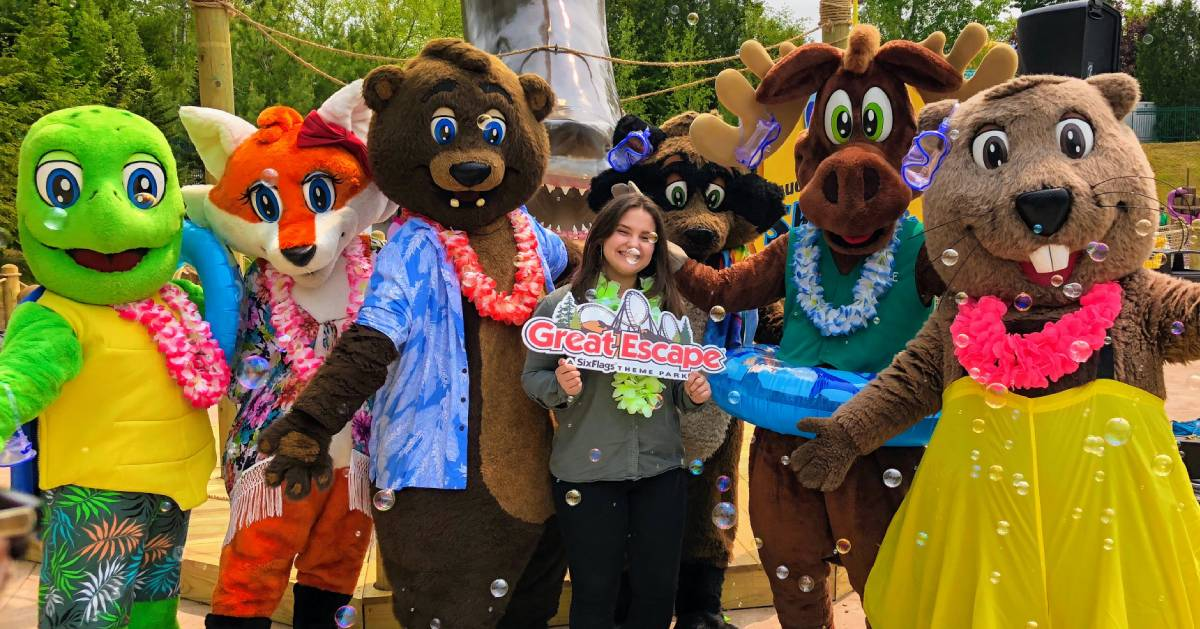 Madison VanDenburg holding up Great Escape sign with costumed animals
