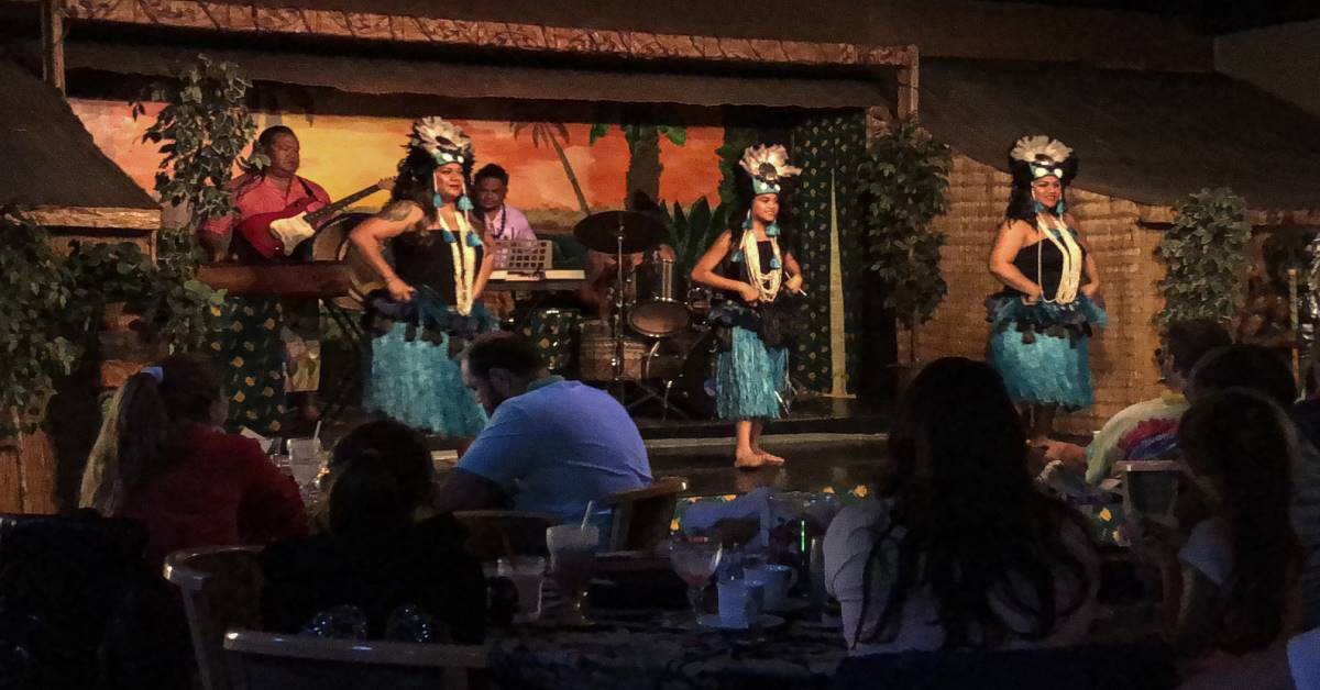 three hula dancers in blue grass skirts