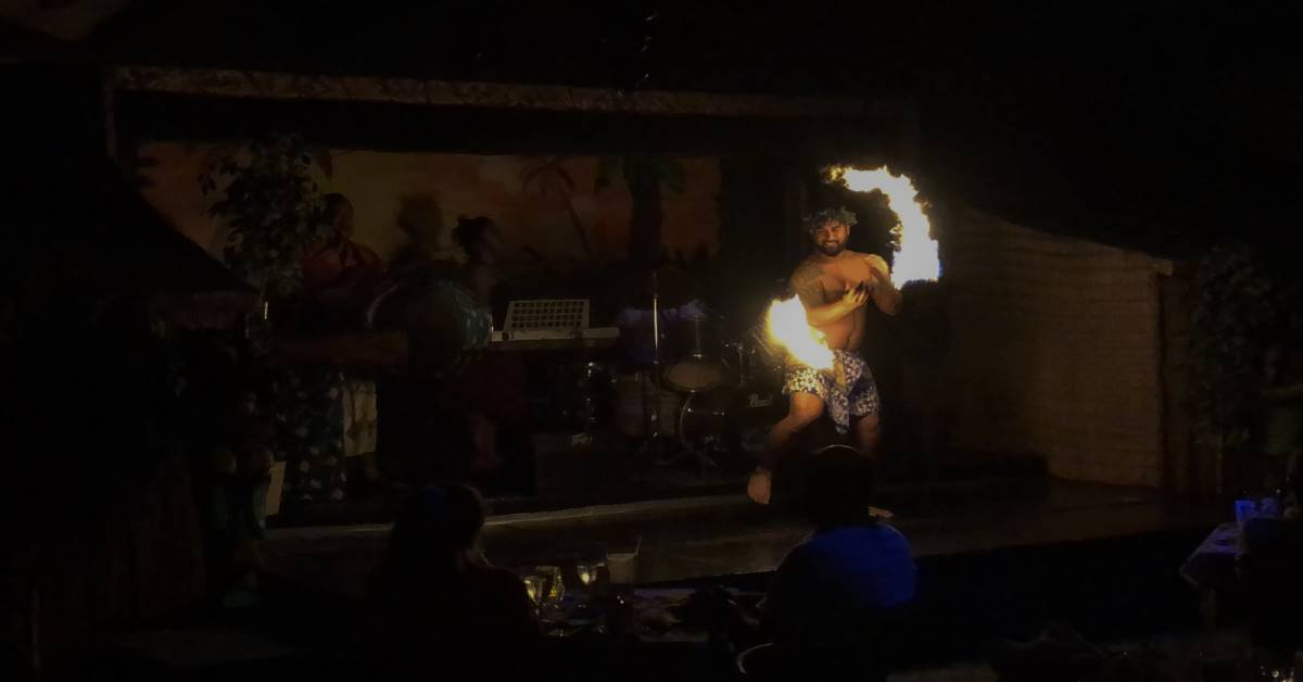 man spinning staff with ends lit on fire