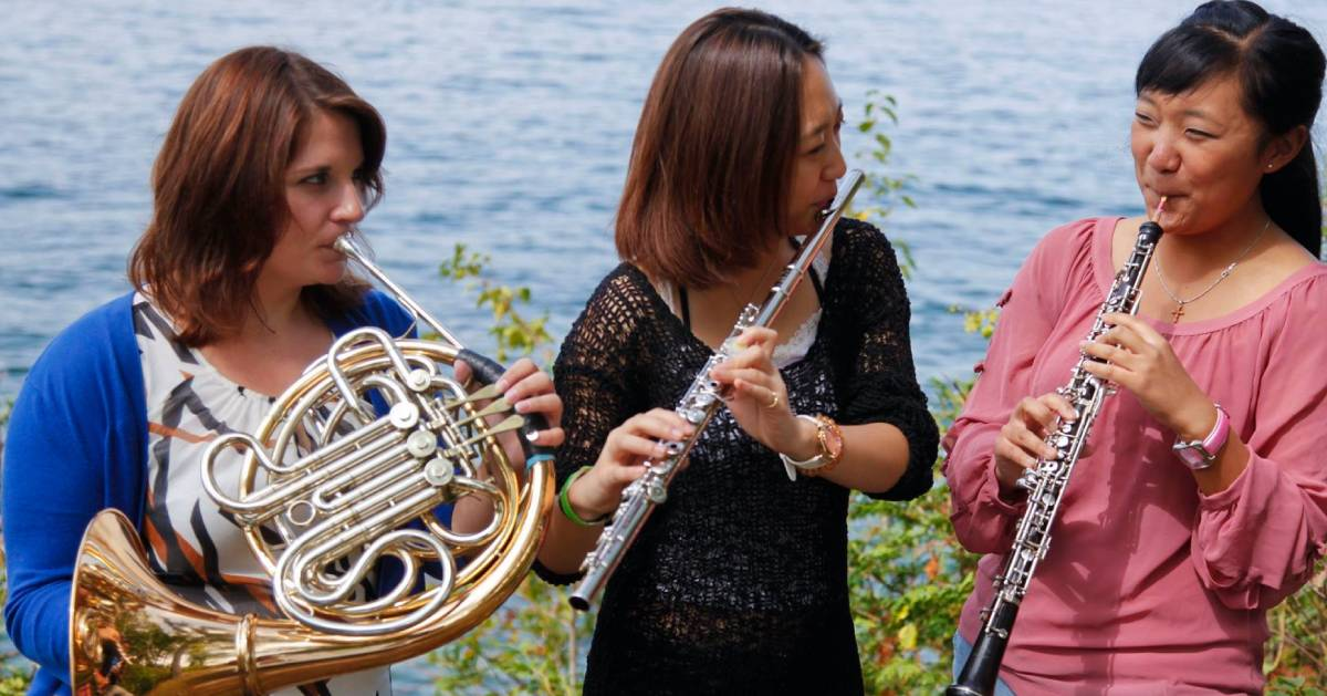 three women playing instruments by the lake