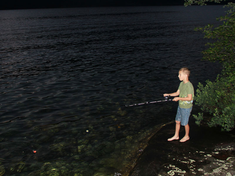 Young boy fishing at dusk from an island on Lake George