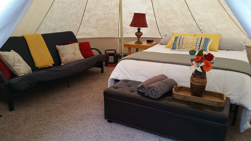 glamping tent with bed, sofa, pillows, and flowers