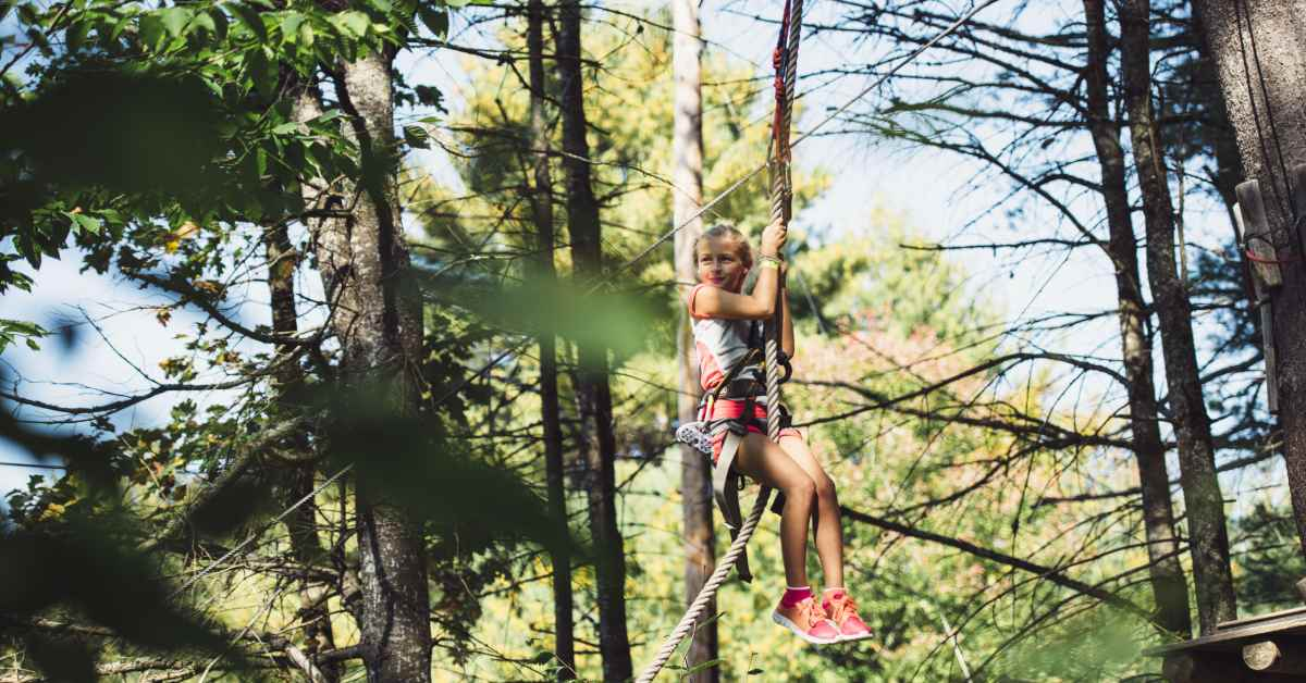 a child on adirondack extreme's adventure course