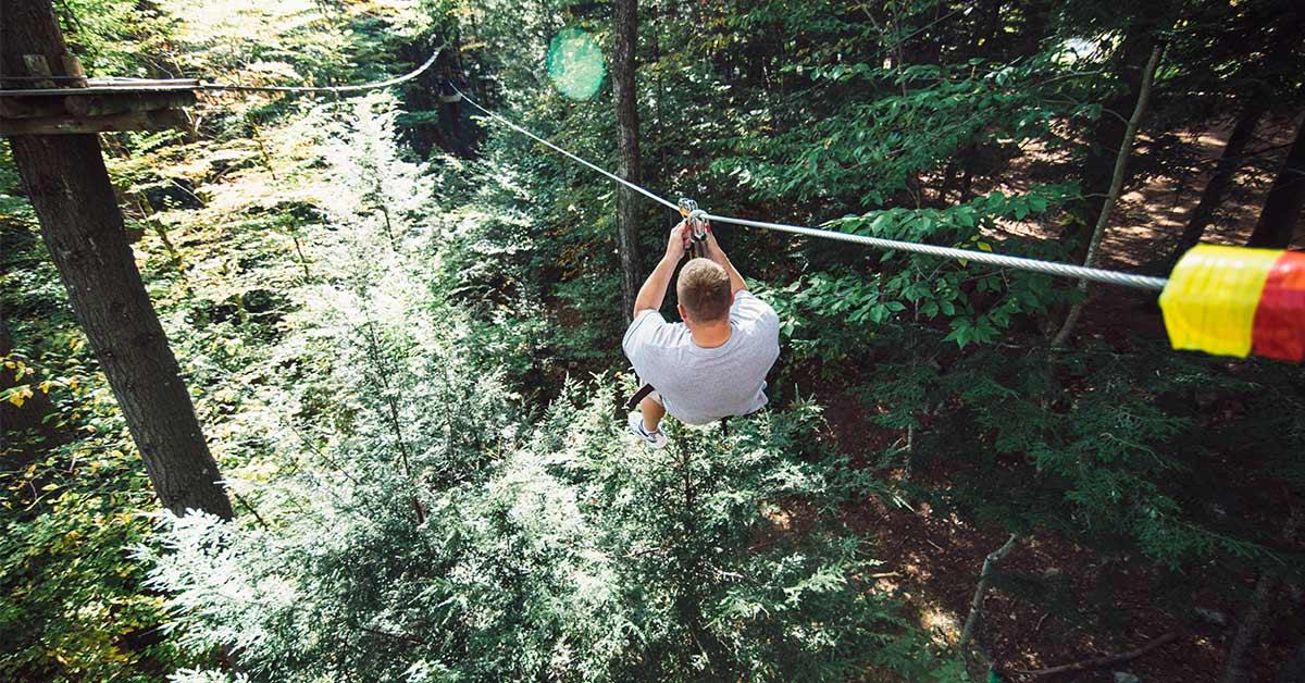 man on a zipline in the woods
