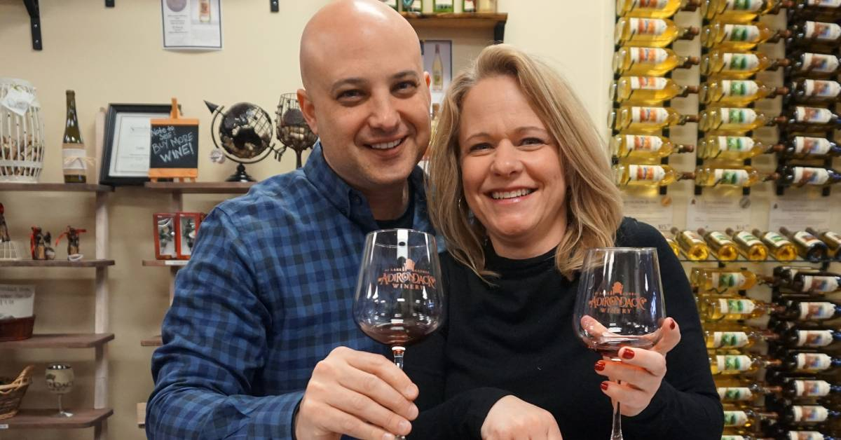 man and woman with wine glasses in a winery tasting room