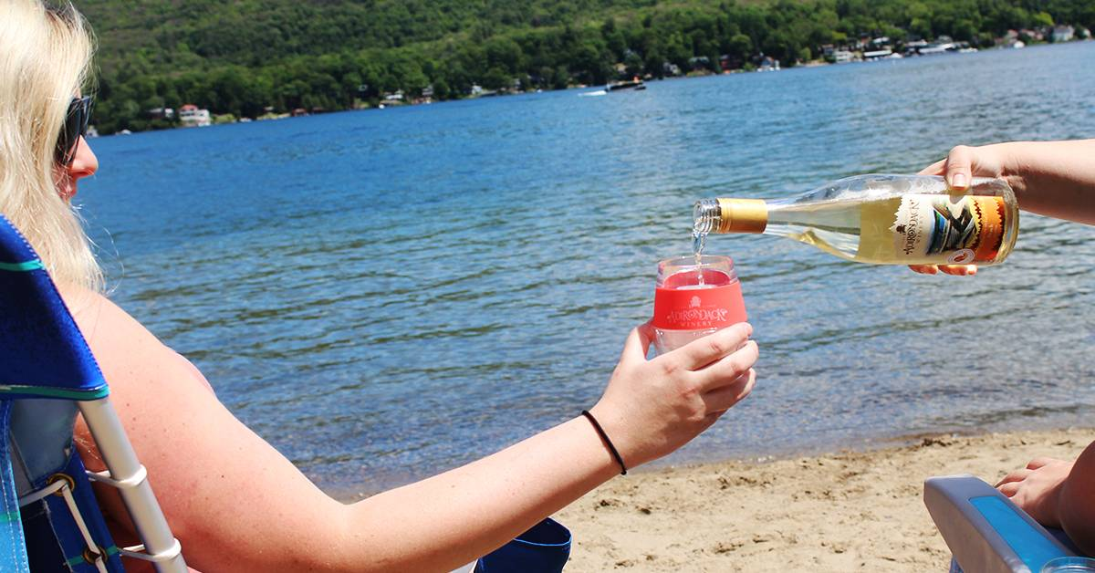one person pouring wine into another person's wine tumbler at the beach