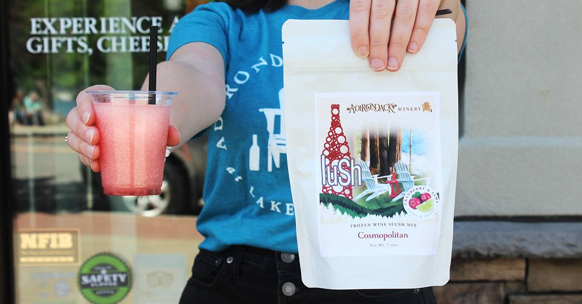 person holding up a wine slushie and a slush mix in a bag