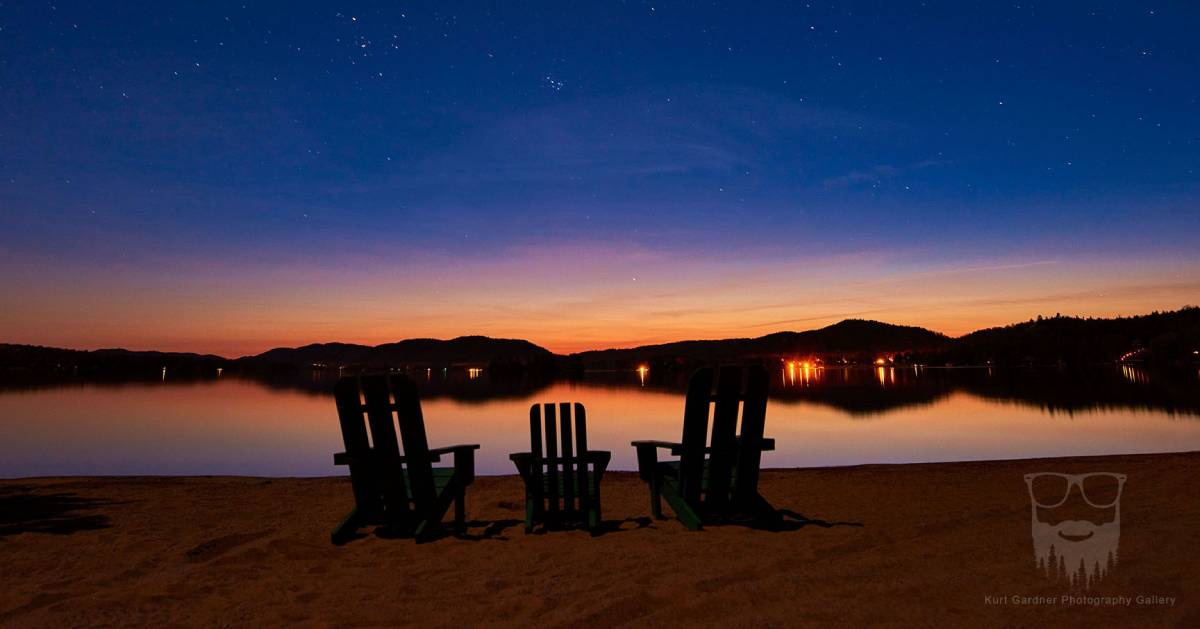 three Adirondack chairs in front of lake at sunset