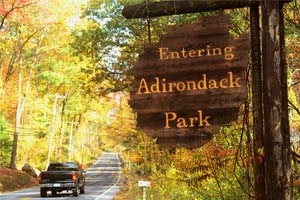 black truck driving by entering adirondack park sign among fall foliage