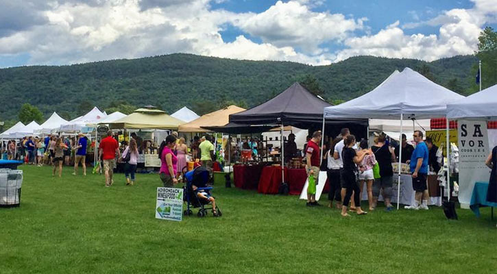 the Adirondack Wine and Food Festival - various tents are set up on a field for all the vendors, there are lots of people, it's a nice day with clouds in the sky, mountain in the background