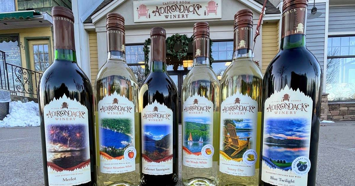 six Adirondack Winery wine bottles displayed in front of store in winter