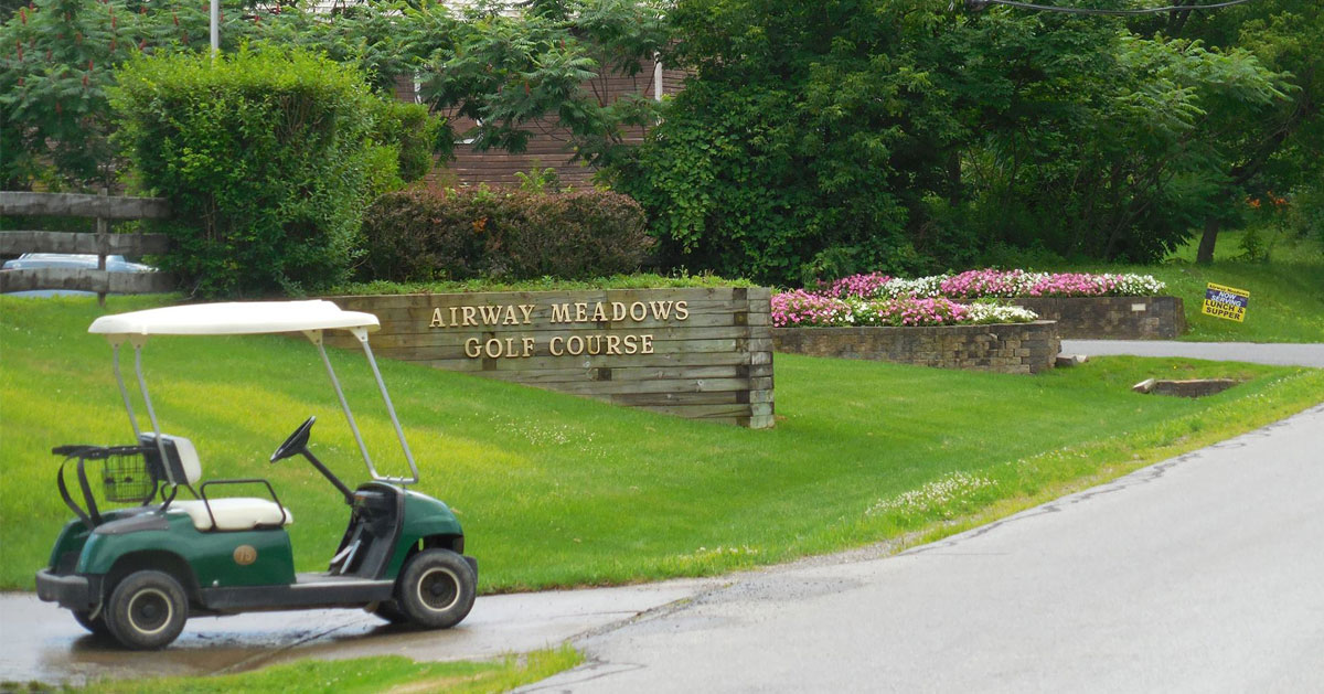 golf cart by Airways Meadow Golf sign