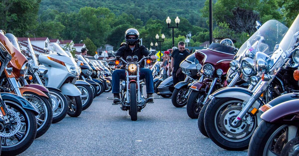 man riding a motorcycle between two rows of parked motorcycles