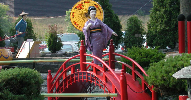 a statue of an Asian woman crossing a bridge as part of the mini-golf course