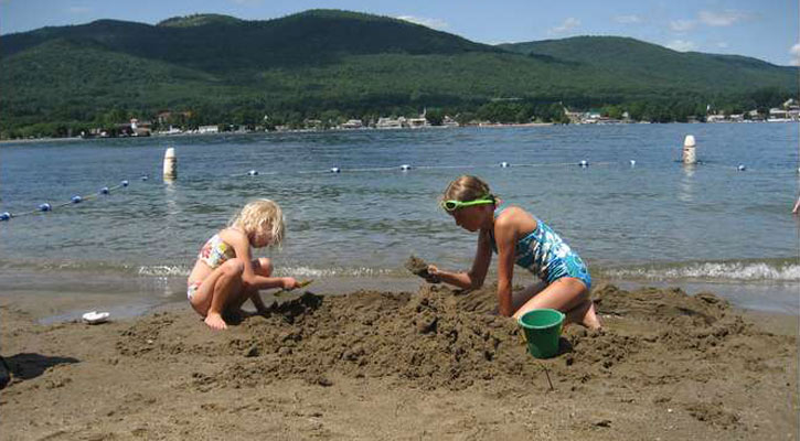 little girls building a sandcastle at the beach
