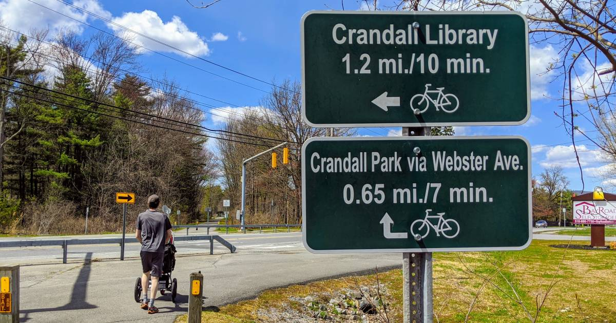 man with stroller on bike path with signage