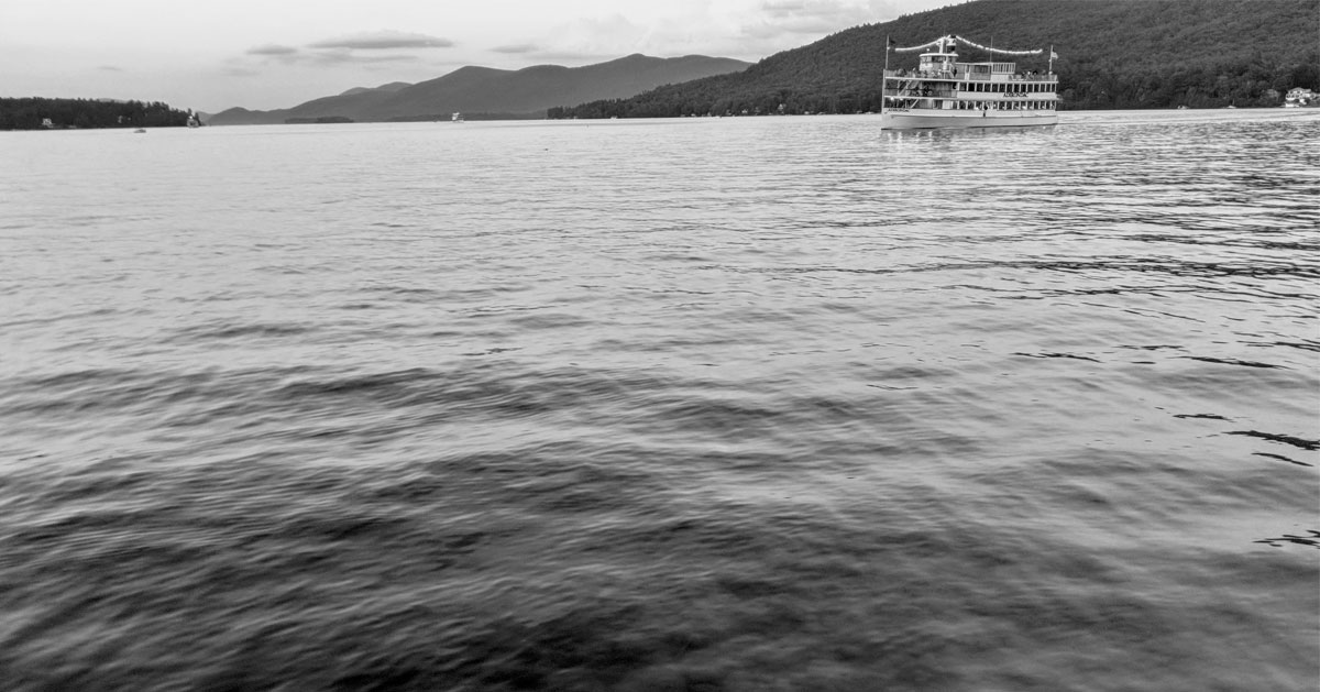 black and white image of steamboat on the lake