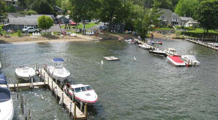 almost an aerial view of boats at the dock, with other docks and properties in view, trees and a mountain in the background