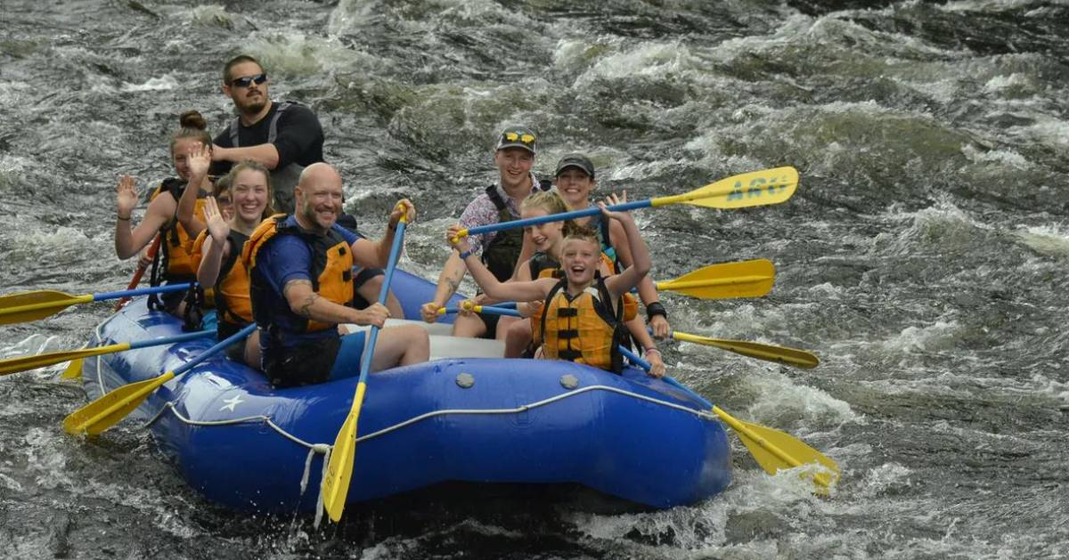 people whitewater rafting in a blue raft