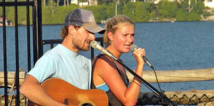 two people singing in front of mikes, water in background