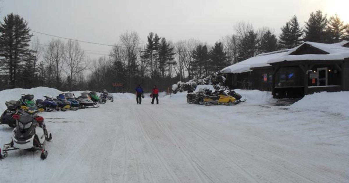 outside of boar's nest bar in winter with snowmobiles
