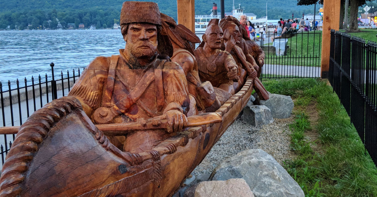statue of Indians and trappers in a boat