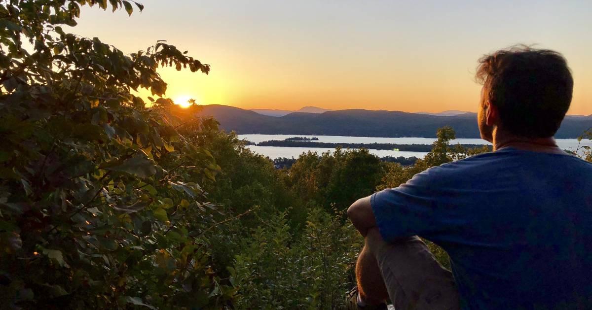 man at summit looking out at sunset