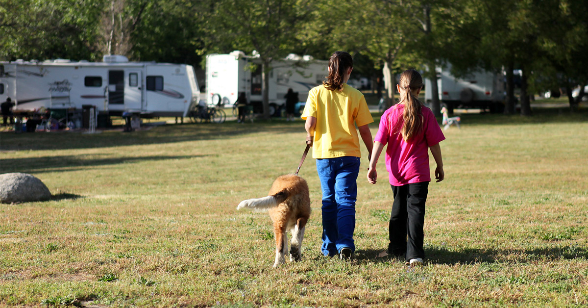 two girls walking a dog at a campground
