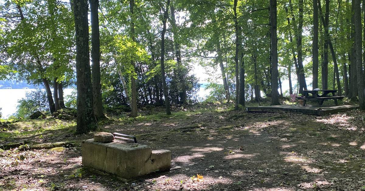 campsite near water, picnic table, fire pit