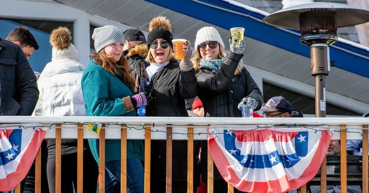 women on balcony cheersing with drinks in winter
