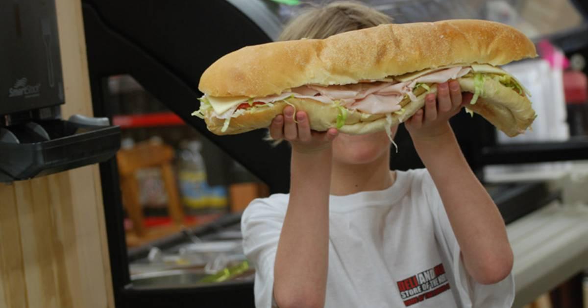 boy holding up a large sub