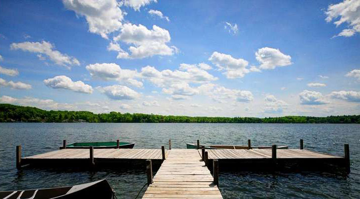 dock that goes out to the left and the right, three rowboats, picturesque image of the lake with trees in the far background and white clouds