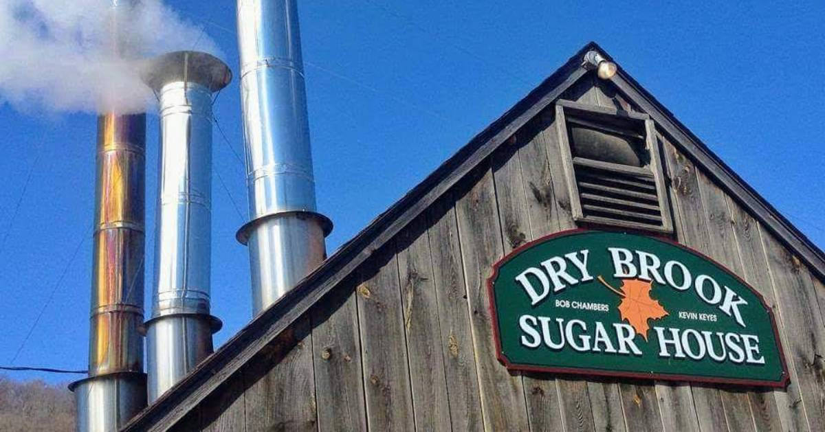 the top of Dry Brook Sugar House with sign and smoke stacks