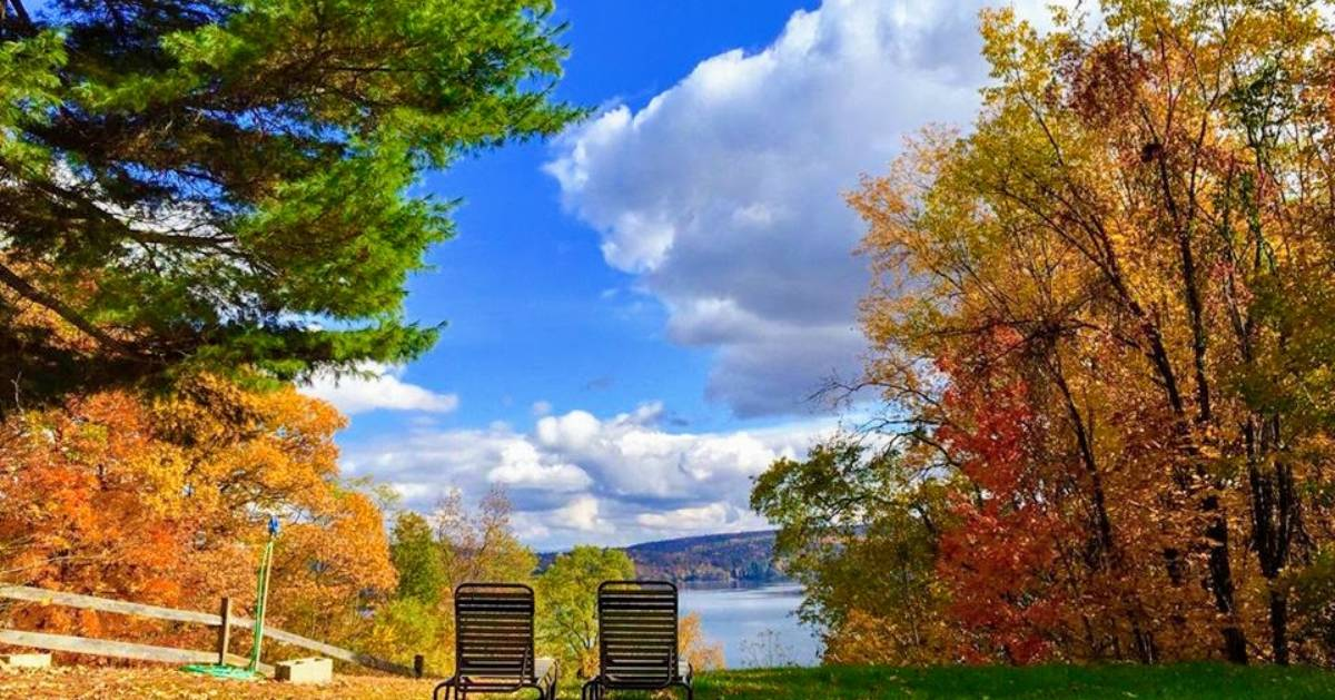view of chairs by lake in the fall