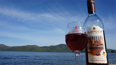 bottle and glass of wine in front of lake george