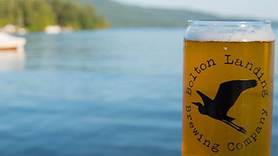 bolton landing brewing company beer in front of a lake