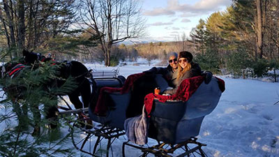two people on a sleigh ride in winter
