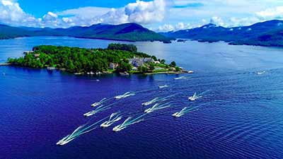 aerial view of several motorized boats on the waters of Lake George