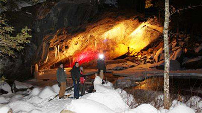 people doing a snowshoe tour at natural stone bridge and caves