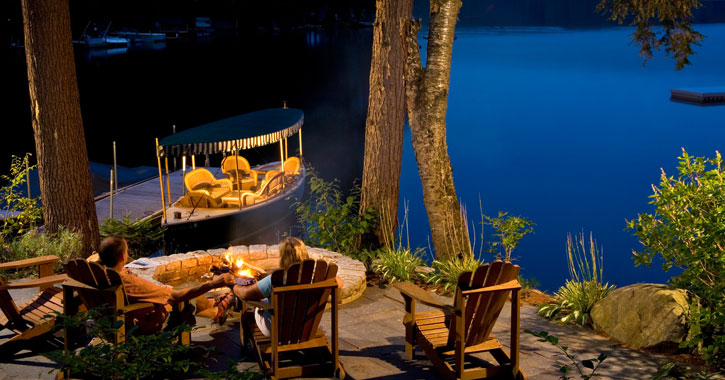 couple in Adirondack chairs by the lake at dusk