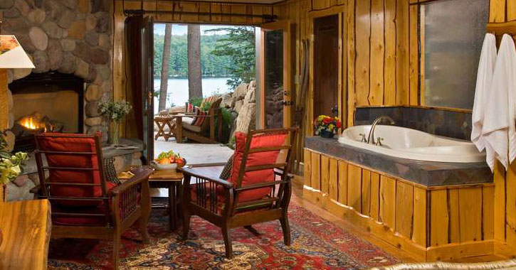 a rustic Adirondack-style room with a fireplace, bathtub, back door opening out onto the water
