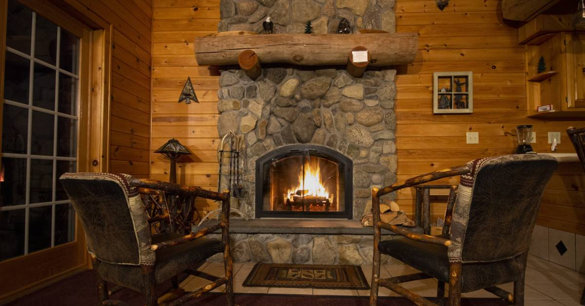 a living room in a cabin with a lit fire