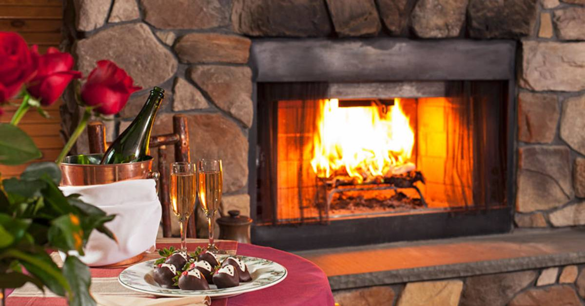 romantic scene with fire in fireplace, champagne, roses, etc.