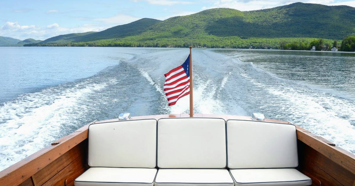 flag on boat with Lake George mountains in background