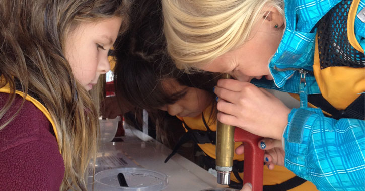two girls, one looking through a microscope