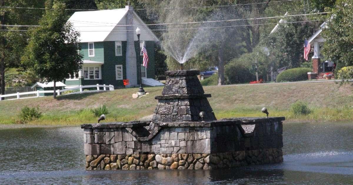 stone fountain spraying water in a lake