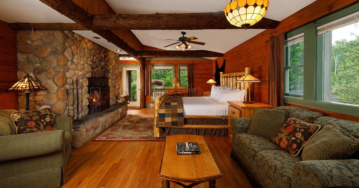 a spacious and rustic hotel room with a bed, stone fireplace, and other furniture